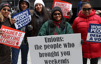 "AFSCME members in Illinois rally with signs that say ""Working people deserve a voice"" and ""Rauner is hurting Illinois."""